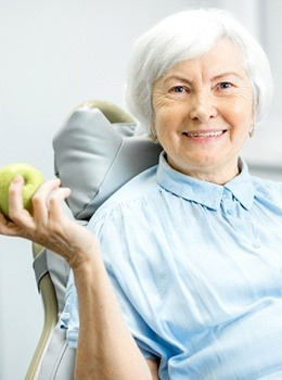 An older woman in the dentist chair holding an apple