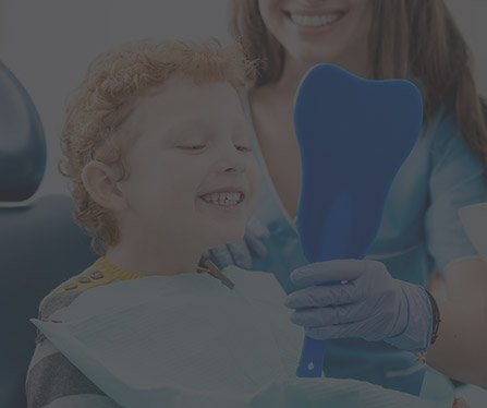 Child in dental chair looking at smile in mirror
