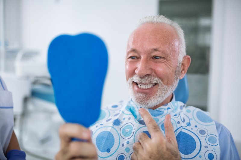 an older man smiling at himself in the mirror at the dentist office