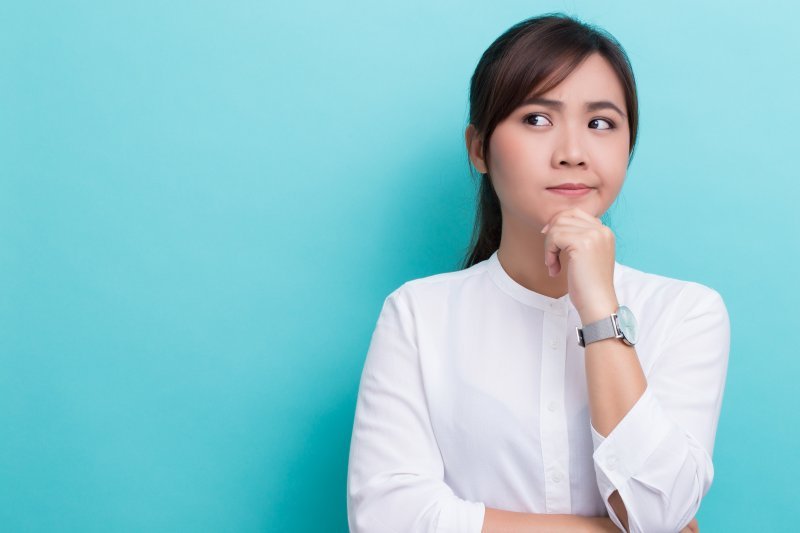 woman thinking about visiting an in-network dentist